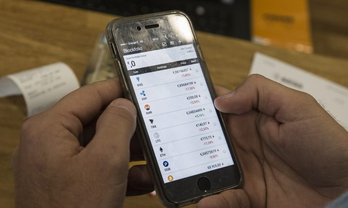 A persons looks at a cellphone displaying virtual currencies exchange rates at La Maison du Bitcoin in Paris on Jan. 17, 2018. (GEOFFROY VAN DER HASSELT/AFP/Getty Images)