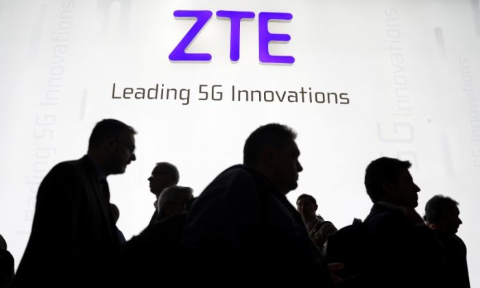 Visitors pass in front of the ZTE booth at the Mobile World Congress in Barcelona, Spain, on February 26, 2018. (Sergio Perez/Reuters)