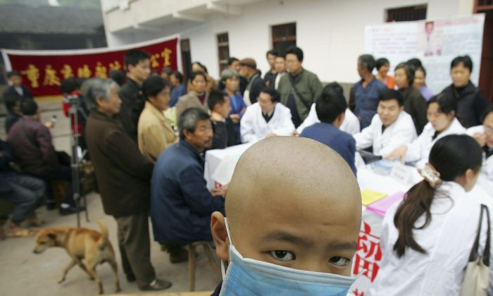 A Chinese boy diagnosed with leukemia wears a mask as he waits for a checkup by cancer specialists in the town of Longshi, in Chongqing City, China, on November 2, 2004. (China Photos/Getty Images)
