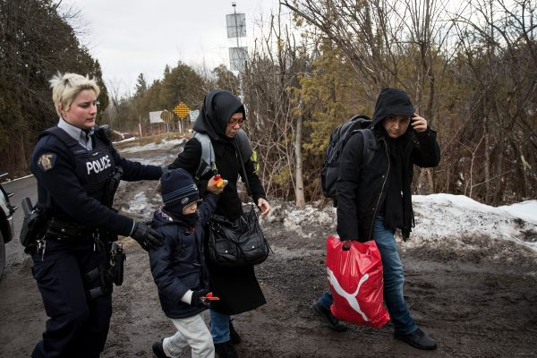 HEMMINGFORD, QUEBEC - FEBRUARY 23: A family of three is escorted to a police vehicle by a Royal Canadian Mounted Police officer after they illegally crossed the U.S.-Canada border into Canada, February 23, 2017 in Hemmingford, Quebec. In the past month, hundreds of people have crossed Quebec land border crossings in attempts to seek asylum and claim refugee status in Canada. (Photo by Drew Angerer/Getty Images)