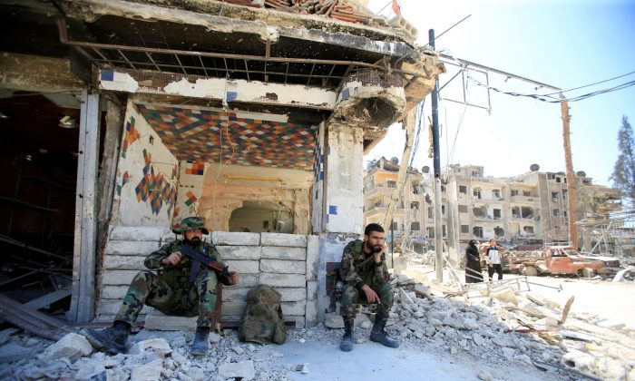 Members of Syrian police sit at a damaged building at the city of Douma, Damascus, Syria April 16, 2018. (Reuters/Ali Hashisho)