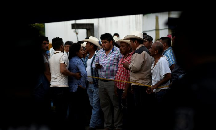 Supporters of slain mayoral candidate Santana Cruz Bahena stand at a crime scene outside his home in the municipality of Hidalgotitlan, in the state of Veracruz, Mexico Nov. 20, 2017. (Reuters/Angel Hernandez)