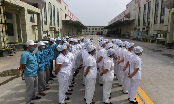 Workers are lined up to sing communist 'red' songs at an instant noodle factory run by Nanjie village, near the village in China's central Henan province on September 29, 2017. (Greg Baker/AFP/Getty Images)