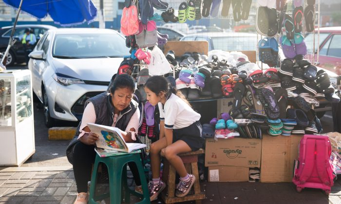 A woman reads with a child near the Mercado Surquillo No.1 in Lima, Peru, on Apr. 16, 2018. (Samira Bouaou/The Epoch Times)