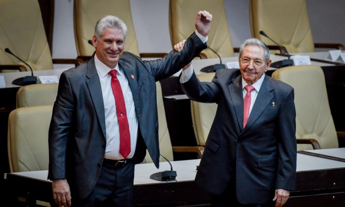 Newly elected Cuban President Miguel Diaz-Canel (L) reacts as former Cuban President Raul Castro raises his hand during the National Assembly in Havana, Cuba, April 19, 2018.(Reuters/Adalberto Roque/Pool via Reuters)