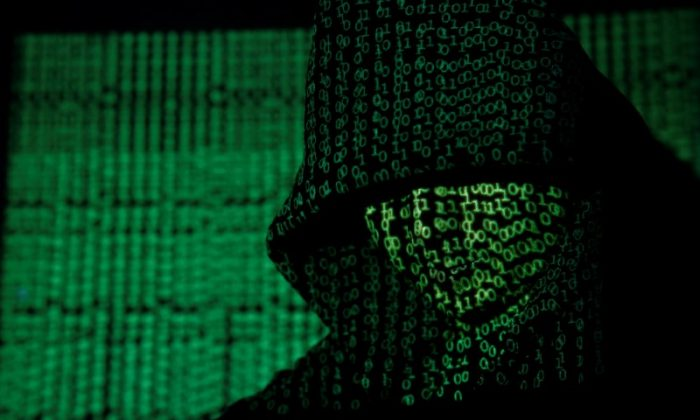 Cyber code on a hooded man on May 13,  2017. (Reuters/Kacper Pempel/Illustration)