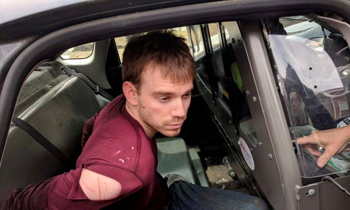 Travis Reinking, the suspect in a Waffle House shooting in Nashville, is under arrest by Metro Nashville Police Department in a wooded area in Antioch, Tennessee on Apr. 23, 2018.  (Courtesy Metro Nashville Police Department/Handout via REUTERS)