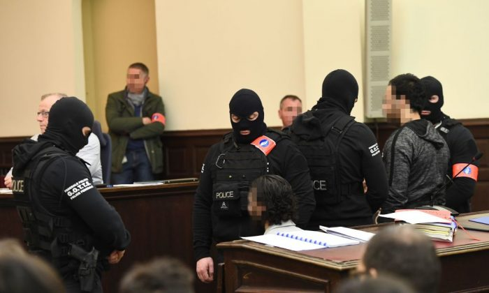 "Prime suspect in the November 2015 Paris attacks Salah Abdeslam (L) sits beside his alleged accomplice Sofiane Ayari (R) as they are surrounded by Belgian special police officers in the courtroom at the ""Palais de Justice"" courthouse in Brussels for the opening of his trial, on February 5, 2018. (Emmanuel Dunand/AFP/Getty Images)"