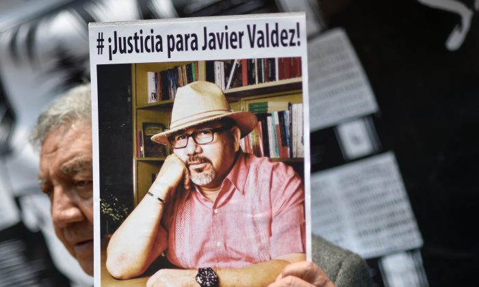 A journalist shows a picture of Mexican journalist Javier Valdez, murdered on the eve, during a protest by journalists in Mexico City on May 16, 2017.  Mexico ranks third in the world for the number of journalists killed, after Syria and Afghanistan, according to media rights group Reporters Without Borders (RSF). (PEDRO PARDO/AFP/Getty Images)