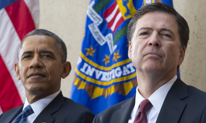 President Barack Obama sits alongside new FBI Director James Comey (R) during an installation ceremony at Federal Bureau of Investigation Headquarters in Washington on Oct. 28, 2013. Comey replaced longtime FBI Director Robert Mueller, who retired after 12 years leading the organization. (SAUL LOEB/AFP/Getty Images)
