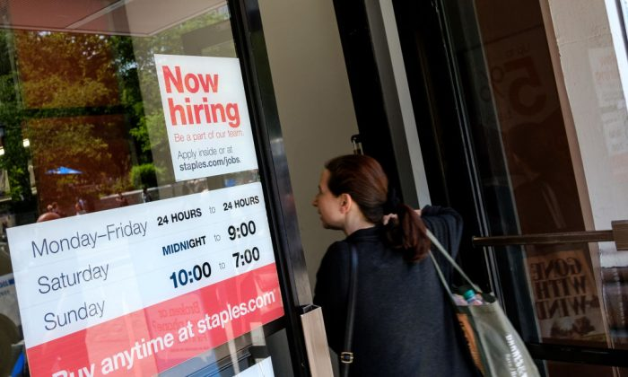 A 'now hiring' sign is displayed on the front entrance to a Staples store in New York City, June 2, 2017. Unemployment in March stayed at 4.1 percent, the lowest level in 17 years. (Drew Angerer/Getty Images)