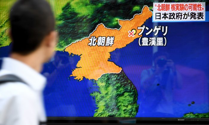 Pedestrians walk past a television screen broadcasting a news program on North Korea's nuclear test in Tokyo, Japan, on September 3, 2017. (Toshifumi Kitamura/AFP/Getty Images)
