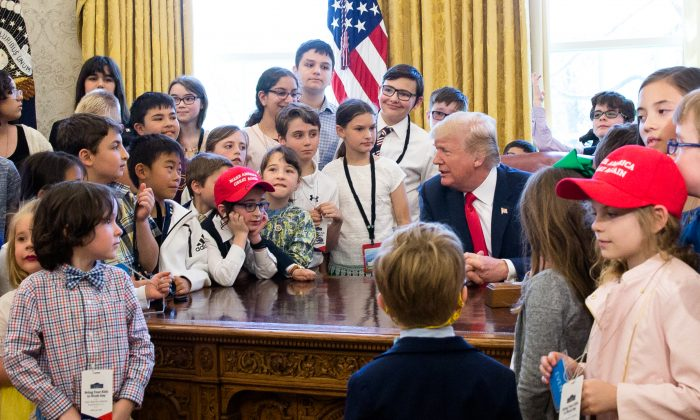 President Donald Trump is surrounded by the children of press and staff  during 'Take your Daughters and Sons to Work Day' in the Oval Office in Washington on April 26, 2018. (Samira Bouaou/The Epoch Times)