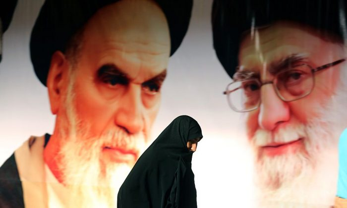 An Iranian woman walks past a giant poster showing supreme leader, Ayatollah Ali Khamenei (R) and the founder of Iran's Islamic Republic, Ayatollah Ruhollah Khomeini (L)  on Feb. 1, 2015 in a suburb of Tehran. (Atta Kenare/AFP/Getty Images)