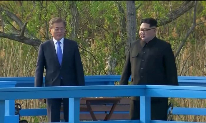 South Korean President Moon Jae-in and North Korean leader Kim Jong Un talk during the inter-Korean summit at the truce village of Panmunjom, in this still frame taken from video, South Korea April 27, 2018. (Host Broadcaster via Reuters TV)