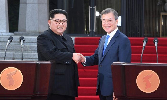 South Korean President Moon Jae-in (R) and North Korean leader Kim Jong Un shake hands at the truce village of Panmunjom inside the demilitarized zone separating the two Koreas, South Korea, April 27, 2018. (Korea Summit Press Pool/Pool via Reuters)