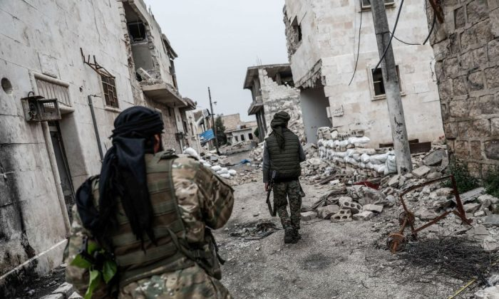 Turkish-backed Syrian fighters walk in a street in Tadef, near the city of al-Bab, in the eastern countryside of Aleppo province on April 27, 2018. (SAMEER AL-DOUMY/AFP/Getty Images)