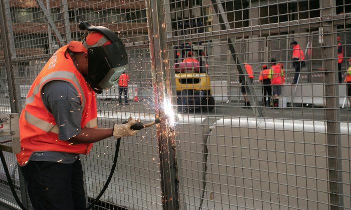 Construction workers weld a barrier together.    (Anoek De Groot/AFP/Getty Images)