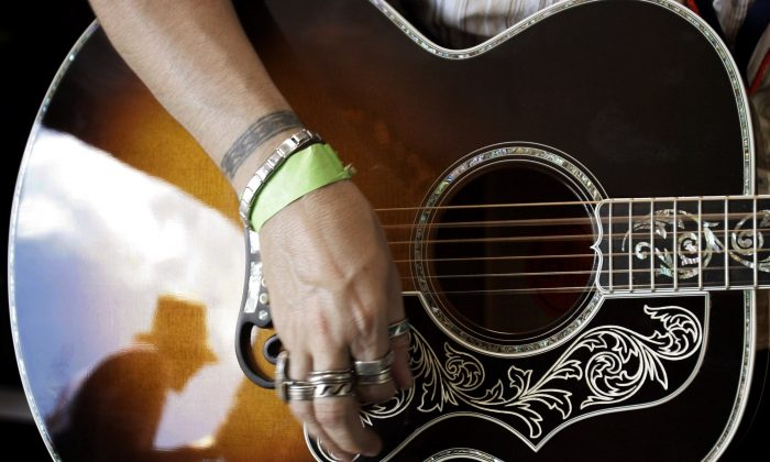 John Roser tries out a Gibson acoustic guitar in the Gibson trailer at the annual Newport Folk Festival in Newport, Rhode Island, U.S., August 5, 2006. (Reuters/Brian Snyder/File Photo)