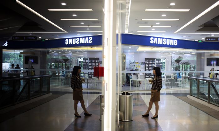 A woman waits for an elevator near a Samsung store in Beijing on May 8, 2015. (Greg Baker/AFP/Getty Images)
