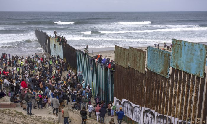 People climb a section of border fence to look into the United States as a caravan of Central American asylum-seekers arrive at the border in Tijuana, Mexico, on April 29. (David McNew/Getty Images)