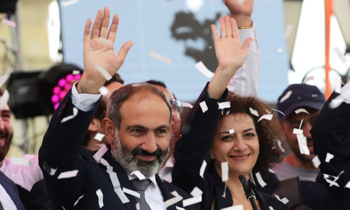 Newly elected Prime Minister of Armenia Nikol Pashinyan (L) greets supporters during a meeting in Republic Square in Yerevan, Armenia May 8, 2018. (Reuters/Hayk Baghdasaryan/Photolure)