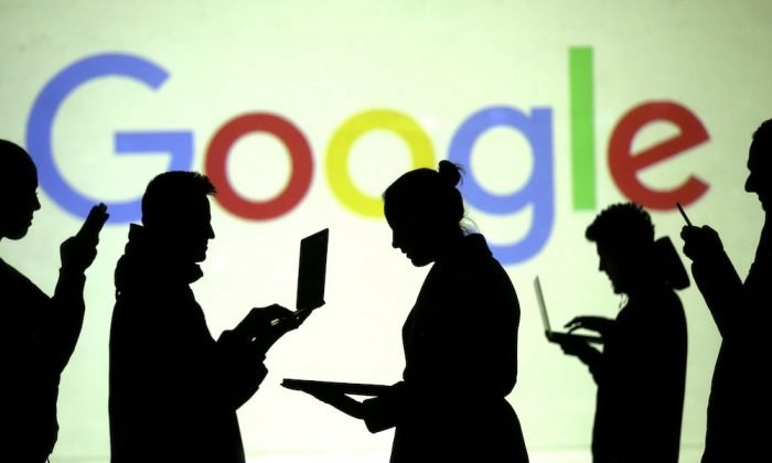 FILE PHOTO: Silhouettes of laptop and mobile device users are seen next to a screen projection of Google logo in this picture illustration taken March 28, 2018.  (REUTERS/Dado Ruvic/Illustration)