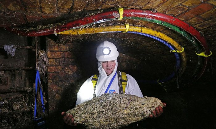 """Tim Henderson, a """"flusher"""" or trunk sewer technician holds a """"fatberg"""" as he works in the intersection of the Regent Street and Victoria sewer in London on Dec. 11, 2014. (Adrian Dennis/AFP/Getty Images)"""