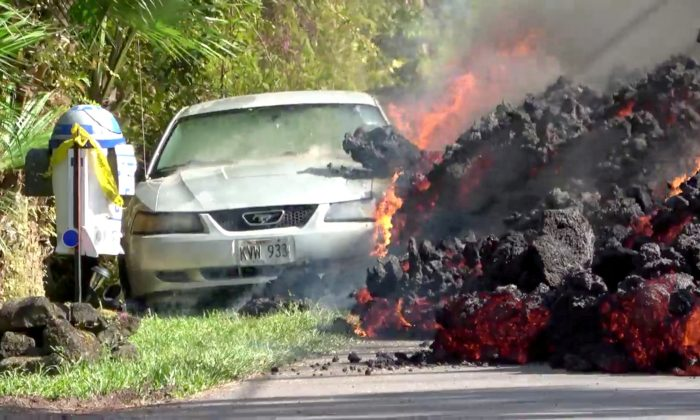 Lava engulfs a Ford Mustang in Puna, Hawaii, U.S., May 6, 2018 in this still image obtained from social media video. WXCHASING via REUTERS