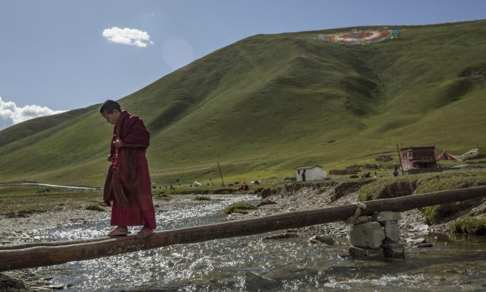 A young Tibetan Buddhist monk walks across a beam over a creek at a monastery next to a government resettlement community for former nomads on the Tibetan Plateau in Yushu County, Qinghai, China, on July 23, 2015. Millions of Tibetans have been forced by the Chinese regime to give up their traditional way of life and resettle in government-designated areas. (Kevin Frayer/Getty Images)