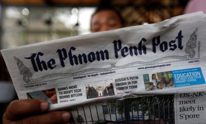 A man reads the Phnom Penh Post newspaper at a coffee shop in Phnom Penh, Cambodia, May 8, 2018. (Reuters/Samrang Pring)