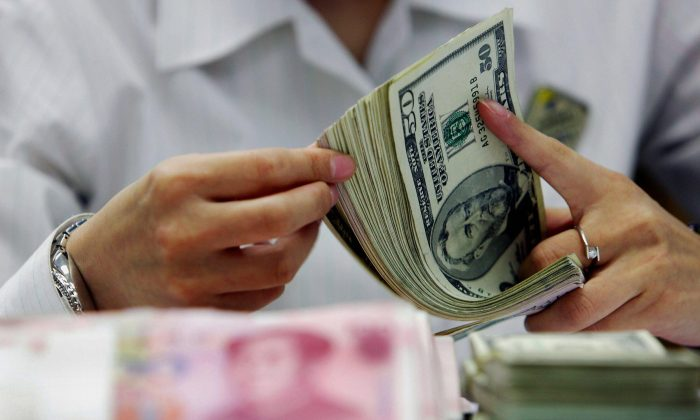 A bank teller counts the stack of Chinese yuan and U.S. dollars at a bank in Shanghai, China on July 22, 2005. (STR/AFP/Getty Images)