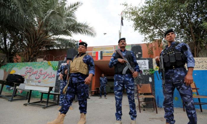 Iraqi security forces stand guard outside a polling station during the parliamentary election in the Sadr city district of Baghdad, Iraq May 12, 2018. (Reuters/Wissm al-Okili)