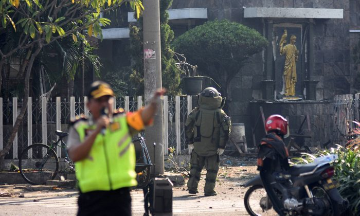 A member of the police bomb squad unit examines the site of an explosion outside the Immaculate Santa Maria Catholic Church, in Surabaya, East Java, Indonesia May 13, 2018,  in this photo taken by Antara Foto. (Antara Foto/M Risyal Hidayat / via Reuters)