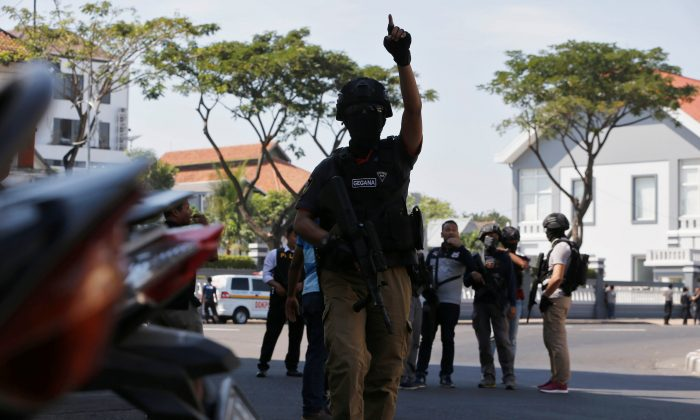 Anti-terror policemen stand guard following a bomb blast at police office in Surabaya, Indonesia May 14, 2018. (Reuters/Beawiharta)