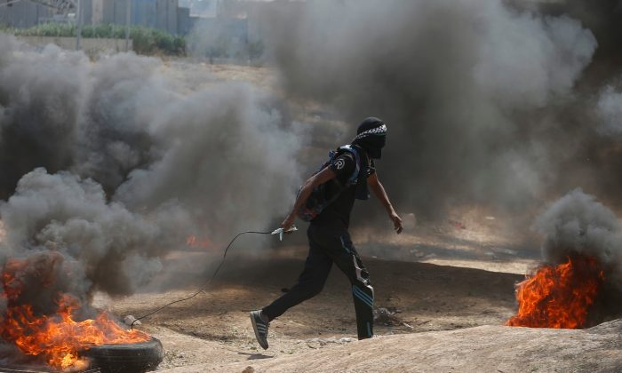 A Palestinian demonstrator drags a burning tire at the Israel-Gaza border, east of Gaza City May 14, 2018. (Reuters/Mohammed Salem)
