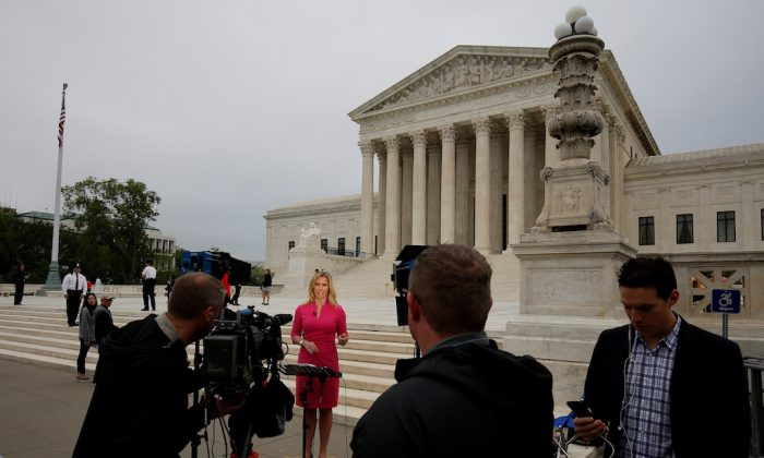 A television journalists reports on a decision that was released allowing the legalization of sports betting at the Supreme Court in Washington on May 14, 2018.      (REUTERS/Joshua Roberts)