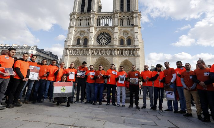 "Members of the ""Association Internationale Solidarite Copte-Europe"" (AISCE, or International Coptic Solidarity Europe) gather on Feb. 22, 2015 outside the Notre-Dame cathedral, to mourn the 21 Egyptian Coptic Christians killed by the ISIS group in Libya. (FRANCOIS GUILLOT/AFP/Getty Images)"