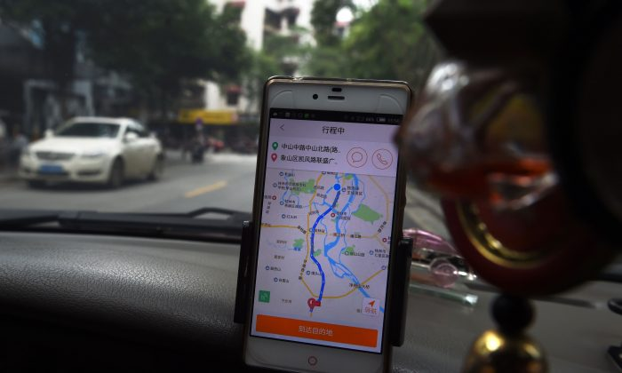 A taxi driver uses the Didi Chuxing app while driving along a street in Guilin City, in China's southern Guangxi Province, on May 13, 2016. (Greg Baker/AFP/Getty Images)