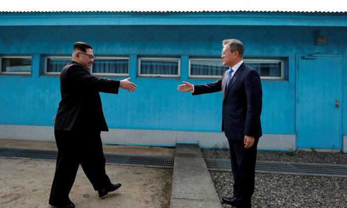 South Korean President Moon Jae-in and North Korean leader Kim Jong Un shake hands at the truce village of Panmunjom inside the demilitarized zone separating the two Koreas, South Korea. (Korea Summit Press Pool/Pool via Reuters)