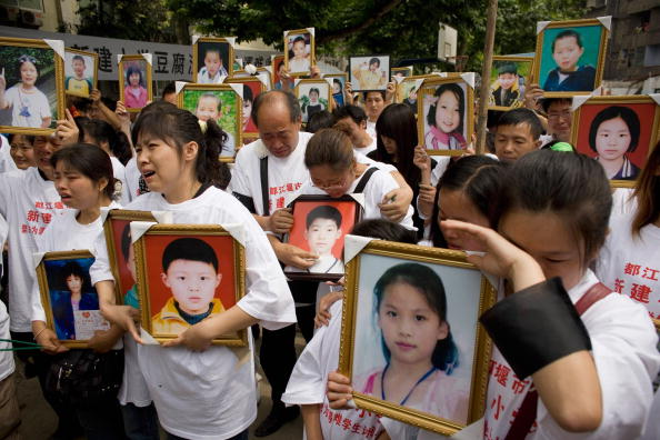 Parents of pupils killed when the Xinjian primary school collapsed in the May 12 earthquake cry as they hold portraits of their loved ones during a commemoration of Children's Day on the rubble-strewn school campus on June 1, 2008 in Dujiangyan, Sichuan province, China. Hundreds of parents and relatives of killed pupils wore T-shirts with the slogan 'Severely Punish Corrupt and Shoddy Construction' during the tearful gathering.  (Andrew Wong/Getty Images)