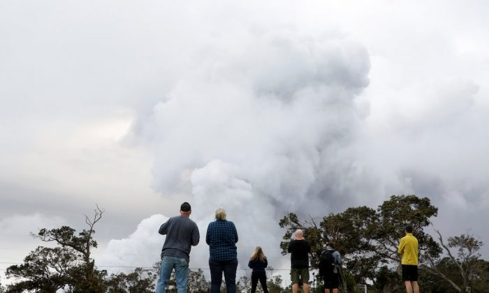 People watch ash erupts from the Halemaumau crater near the community of Volcano during ongoing eruptions of the Kilauea Volcano in Hawaii on May 15, 2018.  (REUTERS/Terray Sylvester)