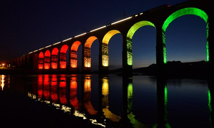 A train travelling on the East Coast mainline is reflected in the River Tweed as it crosses the Royal Border Bridge at dusk, in Berwick-Upon-Tweed in Northumberland, Britain August 22, 2013. (Reuters/Toby Melville/File Photo)