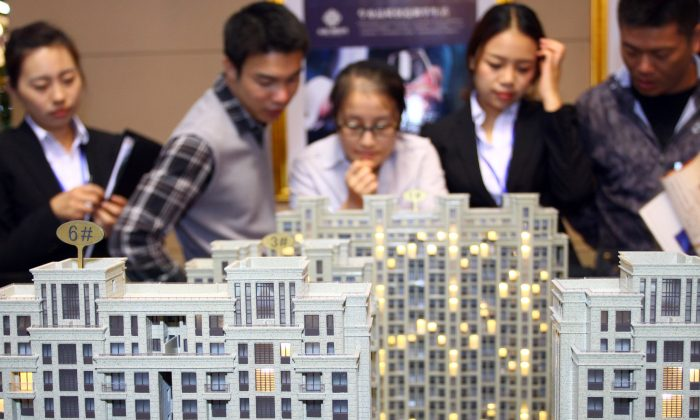Customers and real estate agents looking at several building models at a real estate exhibition in Jiashan County, in eastern China's Zhejiang Province on Oct. 19, 2012. (AFP/Getty Images)
