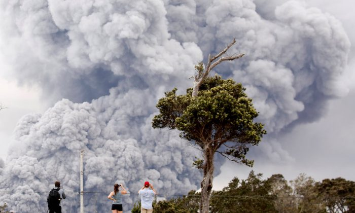 People watch as ash erupts from the Halemaumau crater near the community of Volcano during ongoing eruptions of the Kilauea Volcano in Hawaii on May 15, 2018.  (REUTERS/Terray Sylvester)