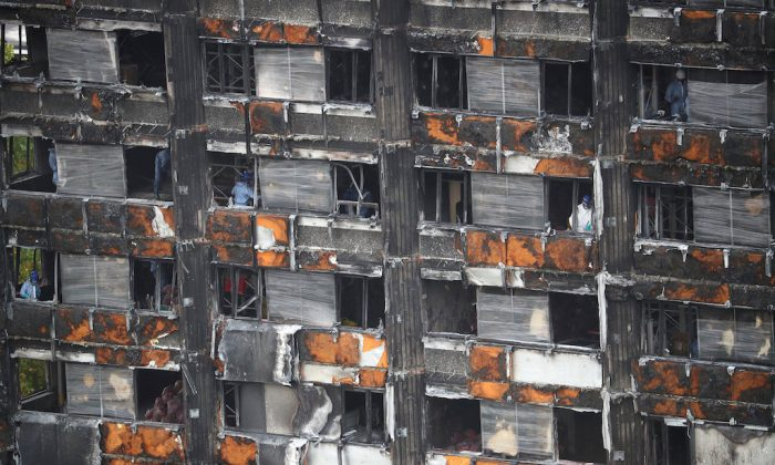 Workers stand inside the burnt out remains of the Grenfell tower in London, Britain, October 16, 2017. (REUTERS/Hannah Mckay/File Photo)