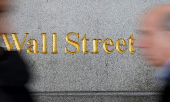 People walk by a Wall Street sign close to the New York Stock Exchange (NYSE) in New York on April 2, 2018. (REUTERS/Shannon Stapleton)