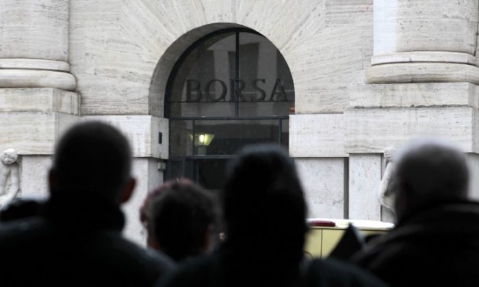 People look at Milan's stock exchange building in downtown Milan March 18, 2013.   (REUTERS/Alessandro Garofalo)