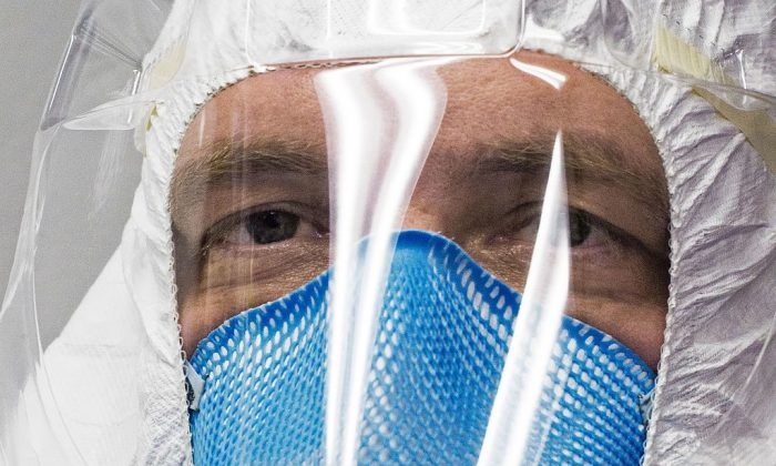 A member of a medical team is seen inside a Containerized Bio-Containment System (CBCS) during a shake-down exercise at Dulles International Airport in Virginia, outside Washington, DC on November 18, 2016 after return with simulated patients infected with Ebola from West Africa.  (Paul J. Richards/AFP/Getty Images)