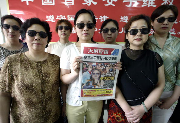 Detectives from China's first all-female detective agency pose for a photograph in their office in Chengdu, China's southwestern Sichuan province 30 April 2004. Armed with sunglasses, binoculars and camcorders, the agency has declared war on wife beaters and unfaithful husbands. (GOH CHAI HIN/AFP/Getty Images)